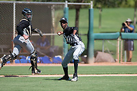 Chicago White Sox relief pitcher Yordi Rosario (59) prepares to make a throw to first base as catcher Evan Skoug (27) follows the play during an Instructional League game against the Kansas City Royals at Camelback Ranch on September 25, 2018 in Glendale, Arizona. (Zachary Lucy/Four Seam Images)