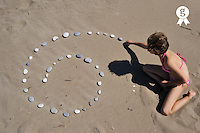 Girl (8) displaying pebbles in spiral shape (Licence this image exclusively with Getty: http://www.gettyimages.com/detail/83676028 )