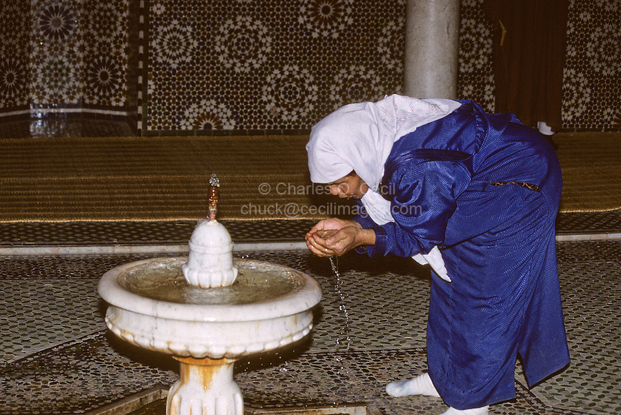 Meknes, Morocco.  Woman drinking from a fountain in the Mausoleum of Moulay Ismail.