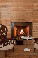 A pair of pony-skin armchairs and a contemporary white side table in front of a roaring fire in the living room