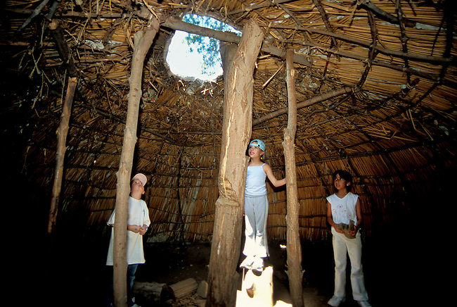 Three children inspect the inside of a dome shaped Chumash house made of brush with a smoke hole is roomy and comfortable. Thousand Oaks California