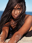 Beautiful young woman with wet long hair lying in the sand at the beach, artistic portrait Image © MaximImages, License at https://www.maximimages.com