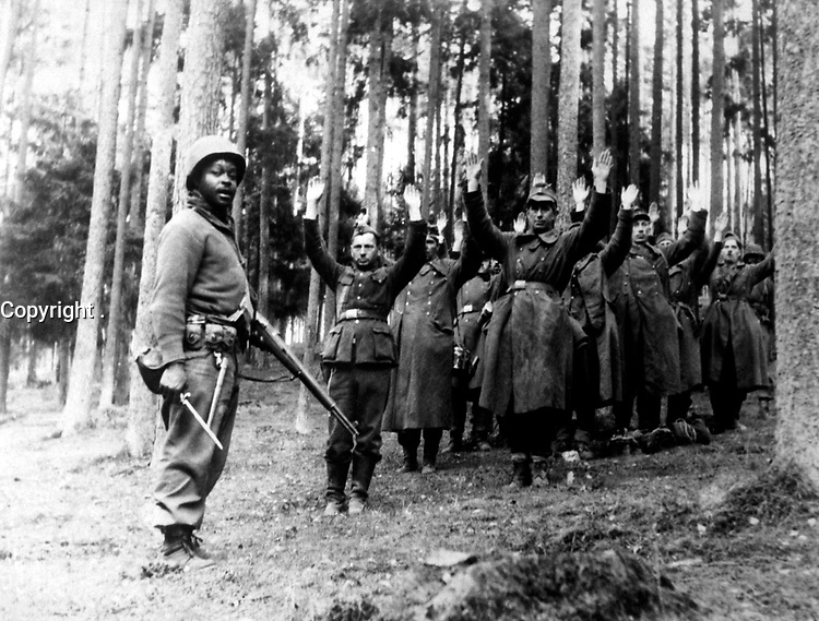 A Negro soldier of the 12th Armored Division stands guard over a group of Nazi prisoners captured in the surrounding German forest.  April 1945.  (OWI)<br /> Exact Date Shot Unknown<br /> NARA FILE #:  208-NP-6QQQ-1<br /> WAR & CONFLICT BOOK #:  1282