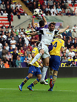 Saturday 28 September 2013<br /> Pictured: Michu of Swansea (in white) batlles for a header against Arsenal goalkeeper Wojciech Szczesny (in purple)<br /> Re: Barclay's Premier League, Swansea City FC v Arsenal at the Liberty Stadium, south Wales.