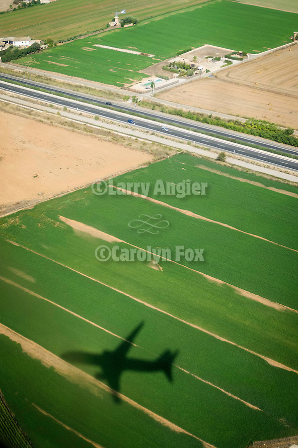 Mallorcan country side from an airline's window seat, Spain. Aircraft shadow on the farmlands on approach to the Palma de Mallorca airport (PMI)