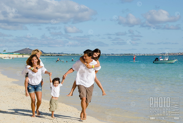 A family of five running down Lanikai Beach, with others in the distance enjoying the water, on O'ahu.