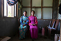 India - Sikkim - Young Lepcha ladies sitting in a traditional house located in the village of Keshel, two hour walk up in the mountain from the closest road.