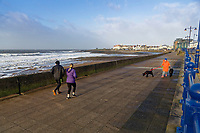 WEATHER PICTURE WALES<br /> Pictured: Two people jog and a woman takes a stroll with her two dogs by the promenade in the seaside town of Porthcawl, south Wales, UK. Wednesday 03 January 2018<br /> Re: Storm Eleanor affects parts of the UK.