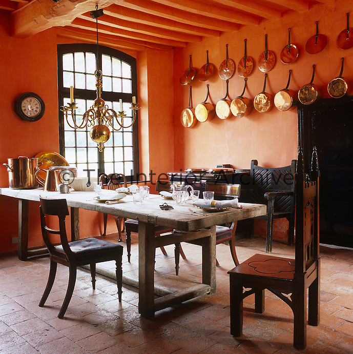 The kitchen is dominated by a scrubbed refectory table and the walls are decorated with copper saucepans original to the chateau