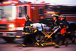 Four EMS personnel running with a cot in front of an engine at a scene