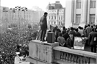 ROMANIA, Pta. Palatului, today Pta. Revolutiei, Bucharest, 22.12.1989<br /> People rise against Ceausescu. After the Ceausescu couple has fled by helicopter around noon, protestors fill the square which originally was guarded by tanks. They aim at the Communist Party Central Committee building. Its balcony is climbed, revolutionary speeches are made. Someone has brought a picture of Timisoara where the revolution started a week earlier leaving many people killed and injured.<br /> © Andrei Pandele / EST&OST