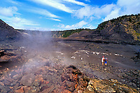 Two hikers walk inside steaming, desolate Kilauea Iki Crater in Volcanoes National Park on the Big Island of Hawaii