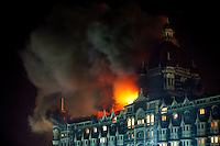 A fire rages over the top floors of the Taj Mahal Palace Hotel after multiple terrorist attacks were launched in Mumbai on 26/11/2008..