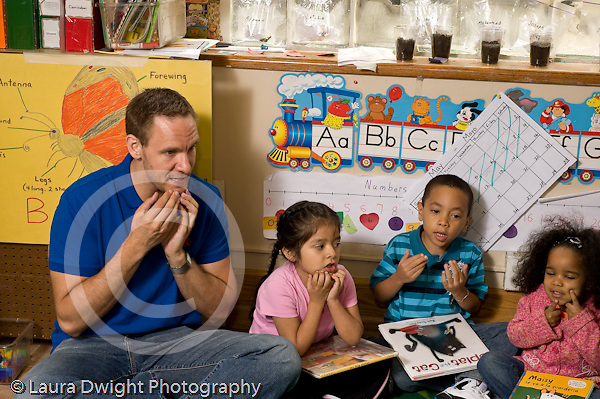 Education preschoool children ages 3-5 circle time male teacher making gesture to chin as part of song boy and girls imitating him horizontal