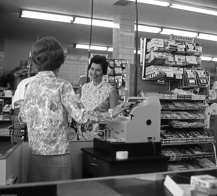 """Bethel Park PA:  View of Marjorie Stewart at the check out counter of Bethel Market Grocery Store. She is being checked out by Millie during an onsite photography assignment for Bethel Market.  Bethel Market was """"the"""" grocery store in Bethel Park from the late 1950s through the early 1980s."""