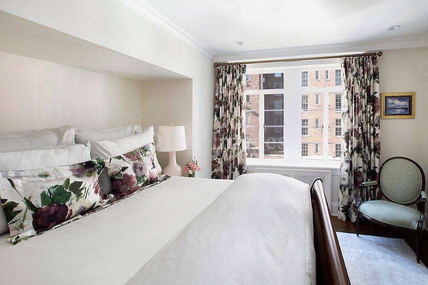 Bed with floral pillows<br /> <br /> First apartment of a young 27 year old who wanted her 1200 sq. ft. apartment in New York City to combine the traditional sensibilities she grew up with in Georgia with the style and taste of a 20-something.