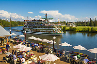 Guests on the deck of the Chena Pump House restaurant watch the Riverboat Discovery pass by on the Chena River, Fairbanks, Alaska.
