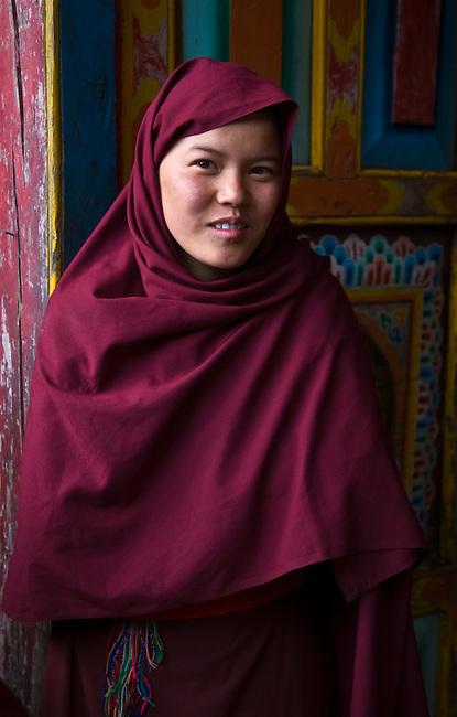 A NUN lives a traditional monastic life studying the dharma at a remote TIBETAN BUDDHIST MONASTERY - NEPAL HIMALALA