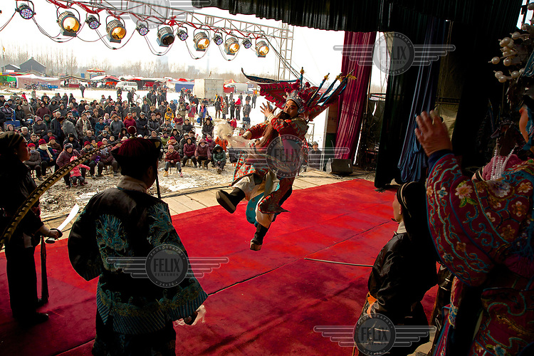 Crowds watch performances on a stage at the Ma Jie folk festival. <br /> <br /> For centuries farmers in Henan have gathered during Chinese New Year in the region's wheat fields to listen to bards singing and recounting old tales. <br /> <br /> Now storytellers come from all over China to attend the annual festival where large crowds gather to watch the best performers.