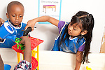 Education preschool first days of school 3-4 year olds boys and girl playing cooperatively at water table wearing smocks boy and girl holding plastic animals as another boy pours water for them