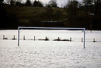 Flooded football field with fence in background