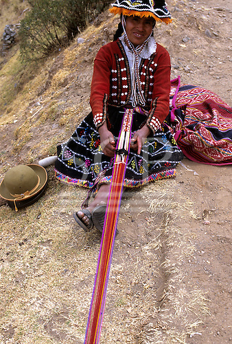 Pisac, Urubamba (Vilcanota) Valley, Peru. Smiling woman in colourful traditional costume weaving a strap.