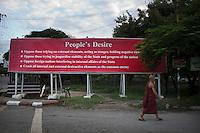 A monk walks past a propaganda poster in central Mandalay.