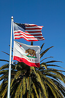 The American and Californian flags fly above Cannery Row, Monterey, California