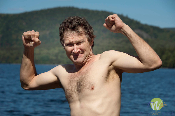 Adult man flexing arms and chest.