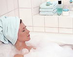 Frau nimmt Schaumbad, entspannt, Augen geschlossen, Handtuch um ihren Kopf gewickelt | woman taking a foam bath, relaxed, eyes closed, towel wrapped around her head