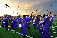Lilli Carmen (right) joins other members of the 2021 senior class at Elkins High School in tossing her mortar board Friday, May 14, 2021, after receiving her diploma during commencement exercises at the school's football field. The school graduated 95 seniors. Visit nwaonline.com/210515Daily/ for today's photo gallery. <br /> (NWA Democrat-Gazette/Andy Shupe)