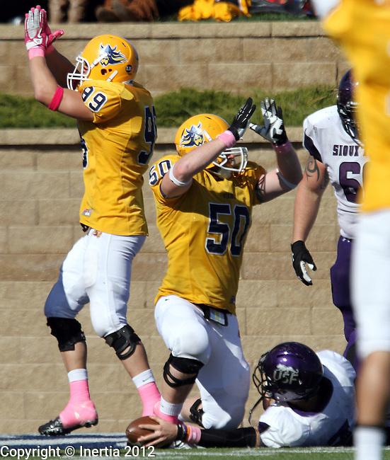 SIOUX FALLS, SD - OCTOBER 20:  Brandon Ordorff #99 and Joel Slinden #50 from Augustana sign for a safety on a sack of Taylor Perkins #7 from the University of Sioux Falls in the second quarter of their game Saturday afternoon at Augustana College. (Photo by Dave Eggen/Inertia)
