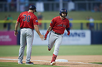 Nick Northcut (24) of the Salem Red Sox slaps hands with third base coach Luke Montz (30) after hitting a home run against the Kannapolis Cannon Ballers at Atrium Health Ballpark on July 29, 2021 in Kannapolis, North Carolina. (Brian Westerholt/Four Seam Images)