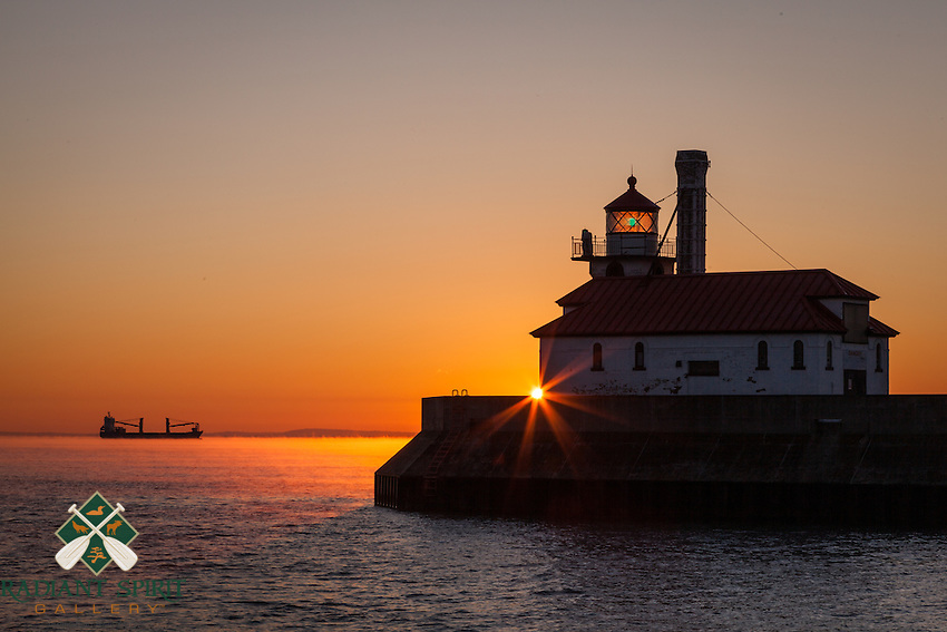 The South Pier Lighthouse is kissed by daybreak. In the distance, the Claude A. DesGagnes awaits at anchor amidst low-lying sea smoke -- a sure sign of the change of seasons.