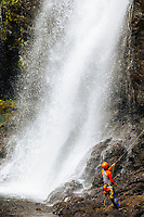 A woman rappels down the side of Kulaniapia Falls until she reaches its base, Big Island of Hawai'i.