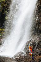 A woman rappels down the side of Kulaniapia Falls until she reaches its base, Big Island of Hawai'i.