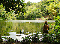 Young woman wading into green lake, a special lush area in the Kapoho area of the Big island