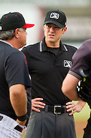Umpire Clayton Hamm meets with Kannapolis Intimidators manager Tommy Thompson (39) at home plate prior to the South Atlantic League game against the Savannah Sand Gnats at CMC-Northeast Stadium on August 20, 2013 in Kannapolis, North Carolina.  The Sand Gnats defeated the Intimidators 5-2.  (Brian Westerholt/Four Seam Images)