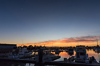 Sunset at the marina, and in the southwest sky, top left, a crescent moon gazes down.
