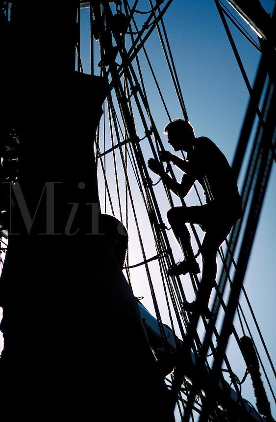 sailor climbing rigging on sailboat. Maine, coastal.