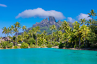 Turquoise lagoon and palm tree forest with Mount Otemanu in the background on Bora Bora paradise island near Tahiti, French Polynesia, Pacific Ocean