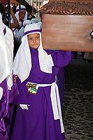 Antigua, Guatemala.  Young Boy Carrying a Float in a Religious Procession during Holy Week, La Semana Santa.