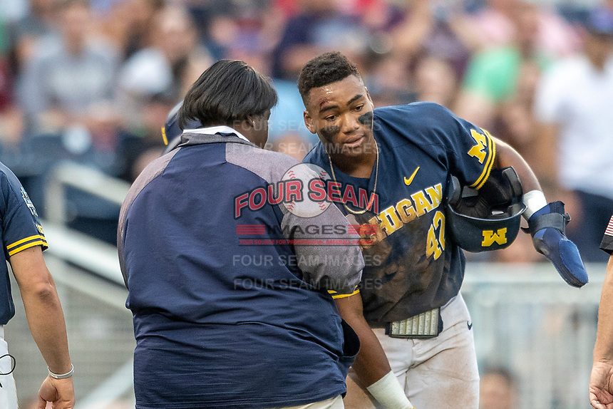 Michigan Wolverines designated hitter Jordan Nwogu (42) talks with team trainer Kimberly Hill after sliding head first into third base during Game 6 of the NCAA College World Series against the Florida State Seminoles on June 17, 2019 at TD Ameritrade Park in Omaha, Nebraska. Michigan defeated Florida State 2-0. (Andrew Woolley/Four Seam Images)