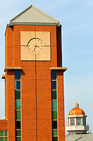 Photography of Charlotte NC's University of North Carolina at Charlotte campus (UNC Charlotte). UNCC, a public university located in northeast Charlotte, is part of the University of North Carolina higher education system. Opened in 1946, the campus has experienced explosive growth in recent years, including the addition of its Charlotte Research Institute campus and a football team. Photo shows the clock tower of the Barnhardt Student Activity Center.