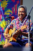 Brother Noland, a musician, performing on stage at the Hawaiian slack key guitar festival smiling