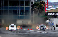 Mar. 11, 2012; Gainesville, FL, USA; NHRA funny car driver Jack Beckman (left) races alongside Alexis DeJoria during the Gatornationals at Auto Plus Raceway at Gainesville. Mandatory Credit: Mark J. Rebilas-
