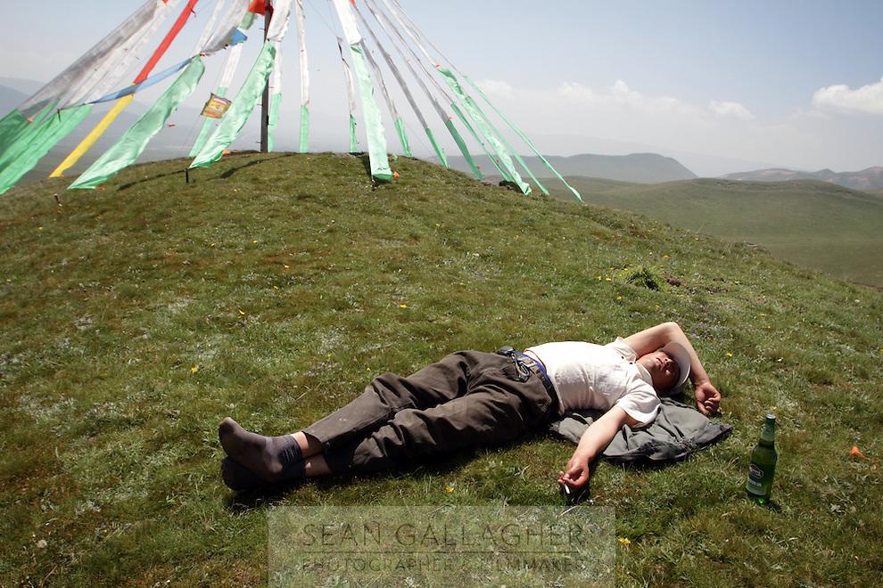 A man sleeps near to Tibetan prayer flags on top of a hill on the Qinghai-Tibetan Plateau, Qinghai Province. China. 2010