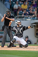 Charlotte Knights catcher Leury Garcia (24) throws the ball back to his pitcher as home plate umpire Shane Livensparger makes a strike call during the game against the Columbus Clippers at BB&T BallPark on May 27, 2015 in Charlotte, North Carolina.  The Clippers defeated the Knights 9-3.  (Brian Westerholt/Four Seam Images)