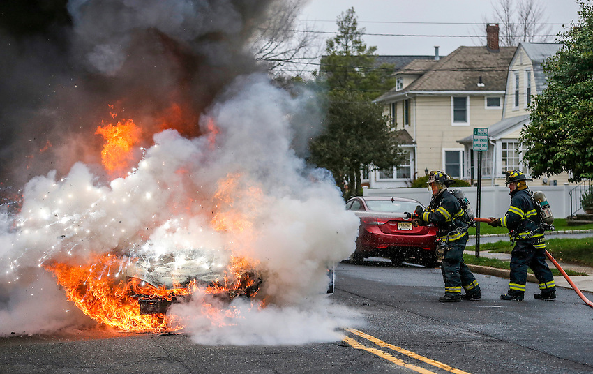 MANASQUAN, NJ — April 1, 2016 —A samll explosion happens as Manasquan firefighters Kevin McCredie and Tom Schofield squirt water on a 2000 Ford Focus that is fully engulfed in flames at about 9:40am on Broad Street, here. The driver of the vehicle, Nancy Trapani, was not injured.  photo by Andrew Mills