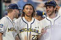 Michigan Wolverines outfielder Jordan Brewer (22) in the dugout with teammates Dominic Clementi (13) and Karl Kauffmann (37) against the Vanderbilt Commodores during Game 1 of the NCAA College World Series Finals on June 24, 2019 at TD Ameritrade Park in Omaha, Nebraska. Michigan defeated Vanderbilt 7-4. (Andrew Woolley/Four Seam Images)